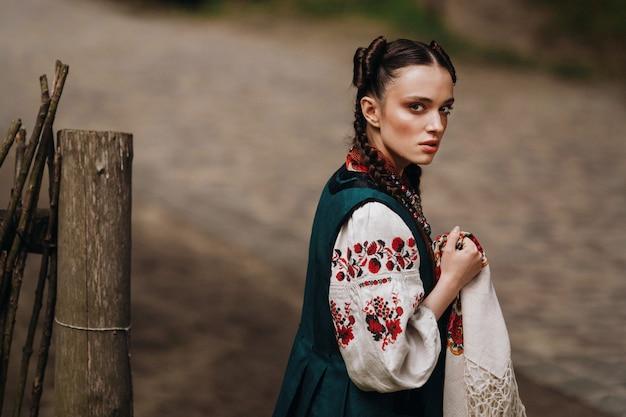 La ragazza harharming in abito tradizionale ucraino sta camminando Foto Gratuite