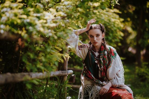 La ragazza in un vestito ucraino tradizionale sta sedendosi su una panchina nel parco Foto Gratuite