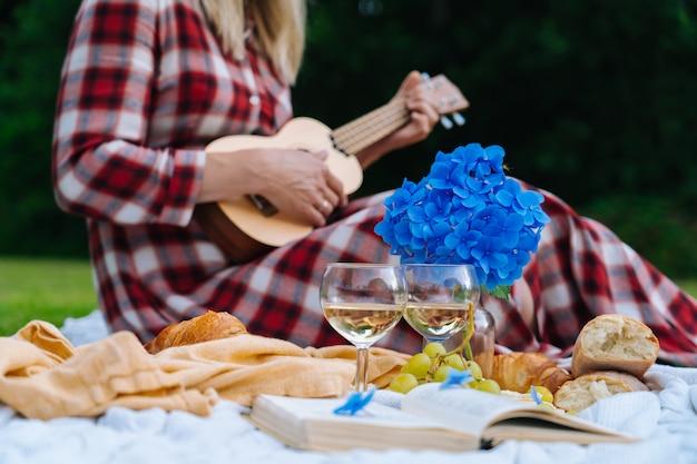 La ragazza in vestito a quadretti rosso e cappello che si siedono sulla coperta di picnic lavorata a maglia bianca gioca le ukulele e beve il vino. picnic estivo in giornata di sole con pane, frutta, bouquet di fiori di ortensia. messa a fuoco selettiva Foto Premium