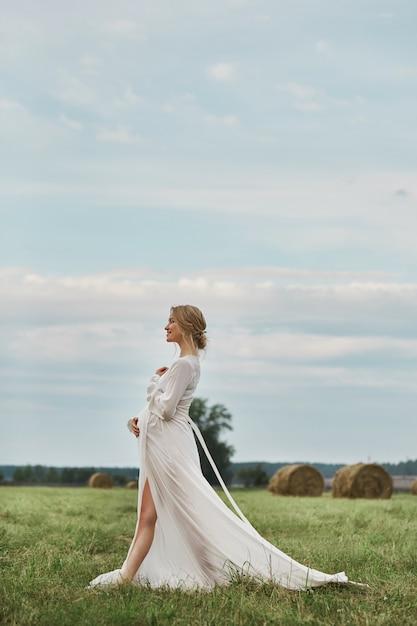 La ragazza incinta cammina in un campo vicino a covoni di fieno in un lungo abito bianco, una donna sorride e si tiene le mani sul ventre Foto Premium