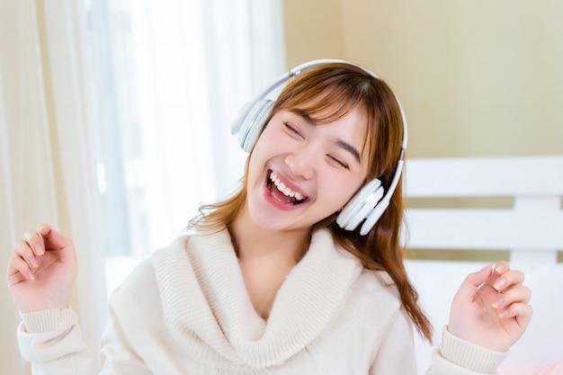 La ragazza indossava le cuffie e si godeva la musica sul letto Foto Gratuite