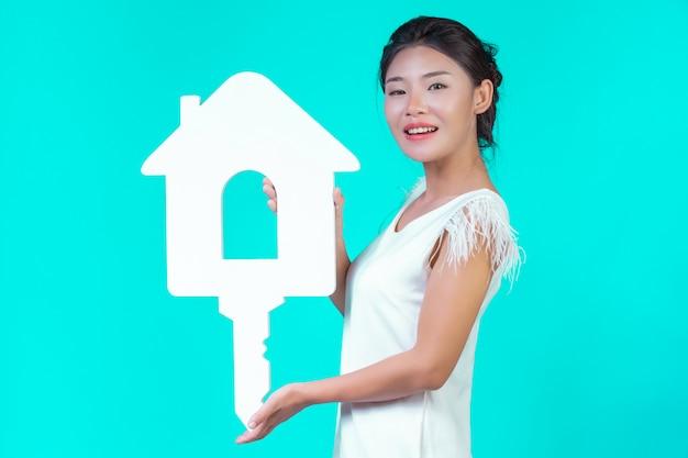 La ragazza indossava una camicia bianca a maniche lunghe con motivi floreali, tenendo in mano il simbolo della casa e mostrando vari gesti con un blu. Foto Gratuite