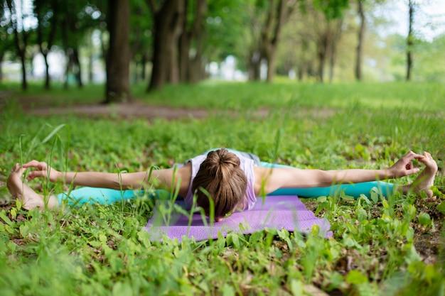 La ragazza magra del brunette fa sport ed esegue yoga belle e sofisticate in un parco estivo. foresta verde lussureggiante sul. donna che fa le esercitazioni su una stuoia di yoga Foto Premium