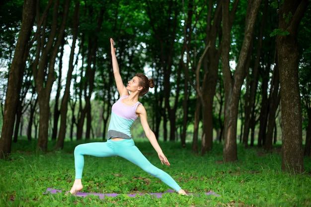 La ragazza magra del brunette fa sport ed esegue yoga belle e sofisticate in un parco estivo. Foto Premium