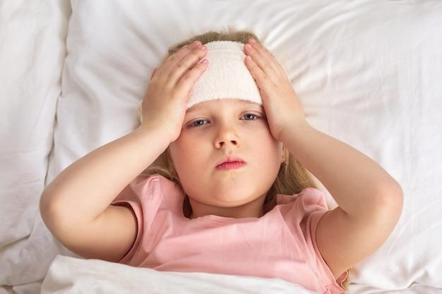 La ragazza malata malata del piccolo bambino si trova a letto Foto Premium
