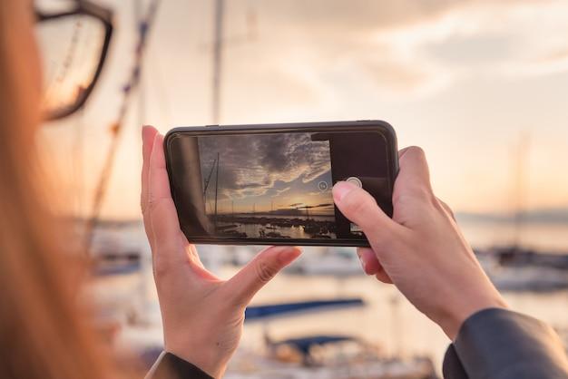 La ragazza prende la foto del porto con gli yacht sullo smartphone al tramonto. viaggio, tema fotografico. Foto Premium