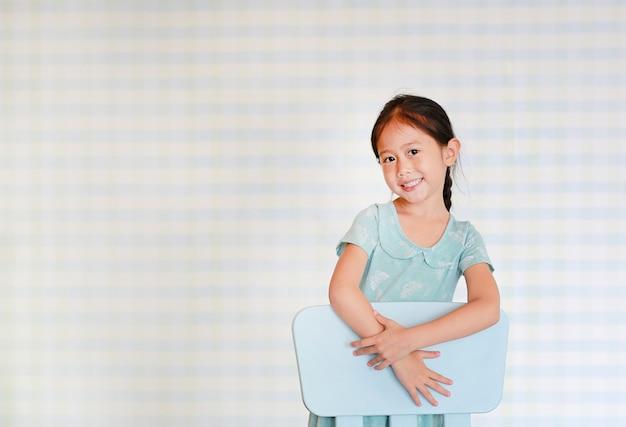 La ragazza prescolare del bambino asiatico felice in una stanza di asilo posa sulla sedia di plastica del bambino. Foto Premium