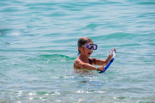 La ragazza prova ad immergersi sott'acqua con il divertimento in mare. persone attive, sport acquatici. lezioni di nuoto durante le vacanze estive. giochi d'acqua. copyspace Foto Premium