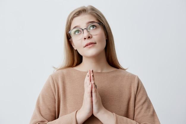 La ragazza religiosa con i capelli biondi in eleganti occhiali preme i palmi delle mani insieme e guarda verso l'alto, pregando dio, chiedendo perdono o chiedendo di realizzare il suo sogno. emozioni e sentimenti Foto Gratuite