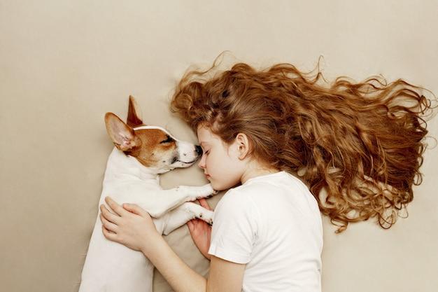 La ragazza riccia dolce e il cane di jack russell sta dormendo nella notte. Foto Premium