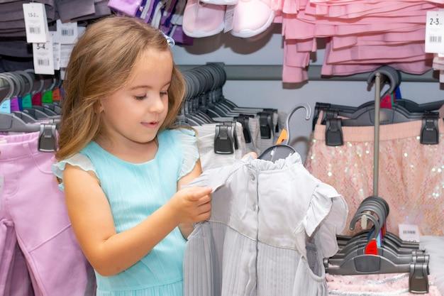 La ragazza sceglie i vestiti in un negozio di abbigliamento. guardando il prezzo Foto Premium