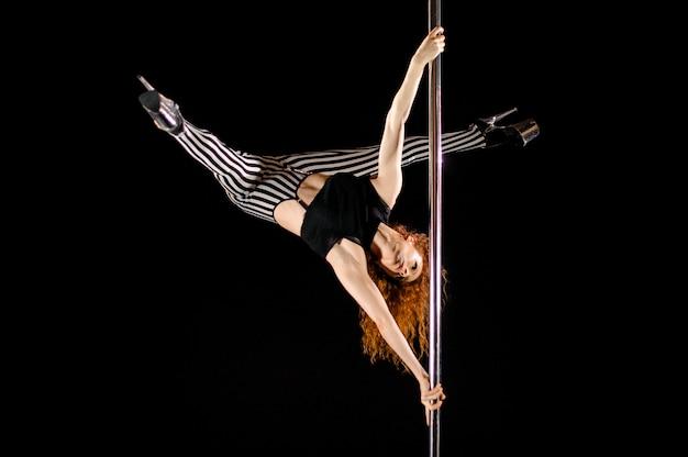 La ragazza sexy di pole dance si esercita e posa sul pilone Foto Premium