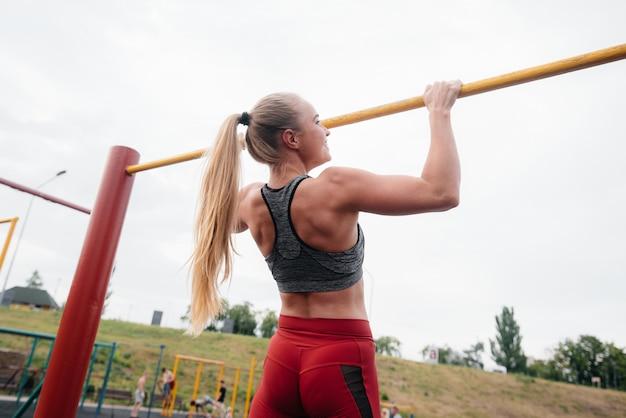 La ragazza sexy è tirata su su una barra orizzontale all'aperto. fitness. uno stile di vita sano Foto Premium