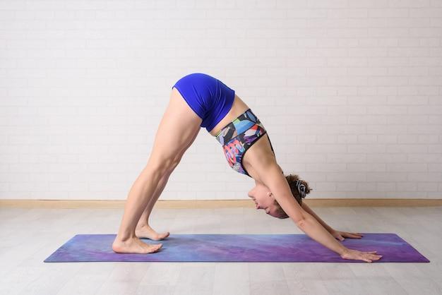 La ragazza si dedica allo yoga. asana adho mukha shvanasana. Foto Premium