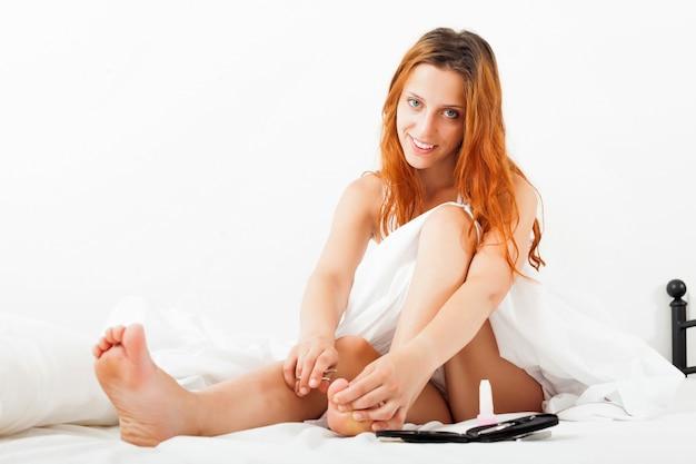 La ragazza si preoccupa per le unghie delle code con le forbici a letto Foto Gratuite