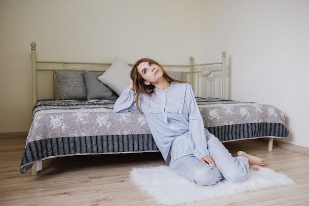 La ragazza si svegliò e si mise in pigiama sul letto nella sua stanza. elegante interno grigio-bianco. Foto Premium