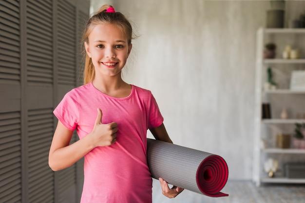 La ragazza sorridente che tiene ha arrotolato la stuoia di esercizio che mostra i pollici su Foto Gratuite