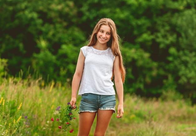 La ragazza sorridente con il campo fiorisce il mazzo Foto Premium
