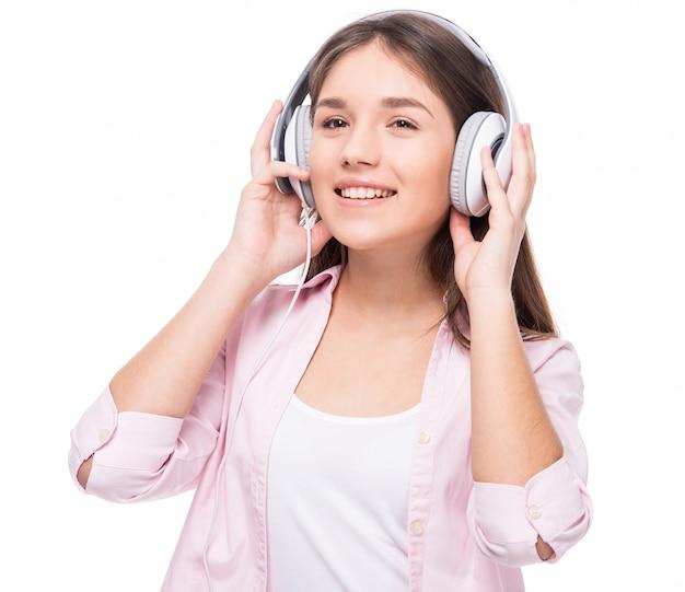 La ragazza sorridente con la cuffia sta ascoltando una musica. Foto Premium
