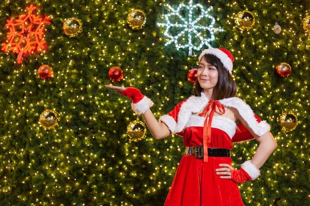 La ragazza sorridente felice della santa è sveglia in vestito rosso con la celebrazione della priorità bassa dell'albero di natale Foto Premium