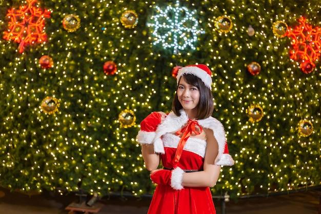 La ragazza sorridente felice della santa è sveglia in vestito rosso con la priorità bassa dell'albero di natale Foto Premium