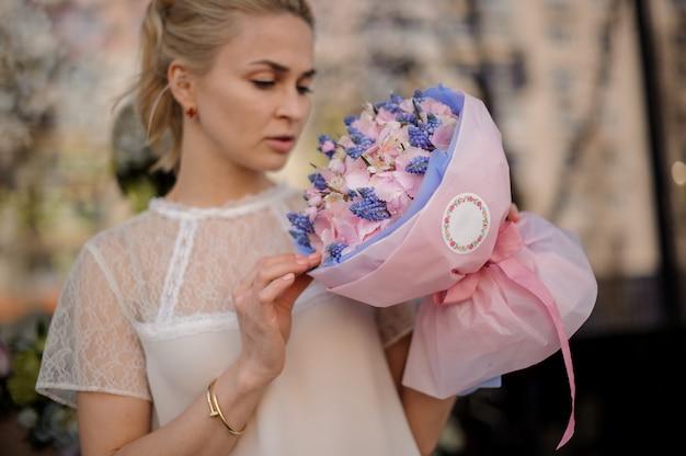 La ragazza sta con il mazzo dei fiori rosa e blu Foto Premium