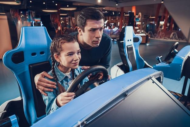 La ragazza sta guidando un'auto in sala giochi. padre sta tifando e aiutando Foto Premium