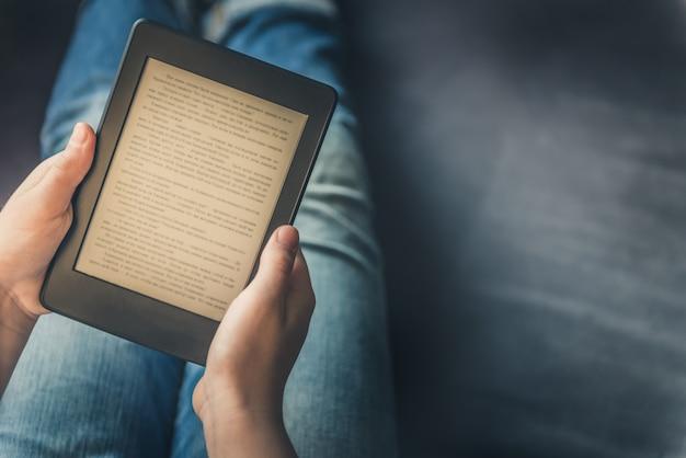 La ragazza sta leggendo ebook sul dispositivo tablet digitale Foto Premium
