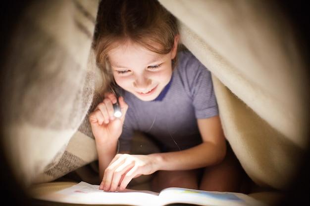 La ragazza sta leggendo un libro sotto una coperta con una torcia elettrica in una stanza buia di notte Foto Premium