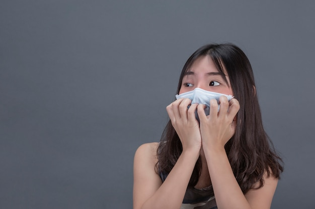 La ragazza sta meditando la maschera mentre copriva a mano sulla parete grigia. Foto Gratuite
