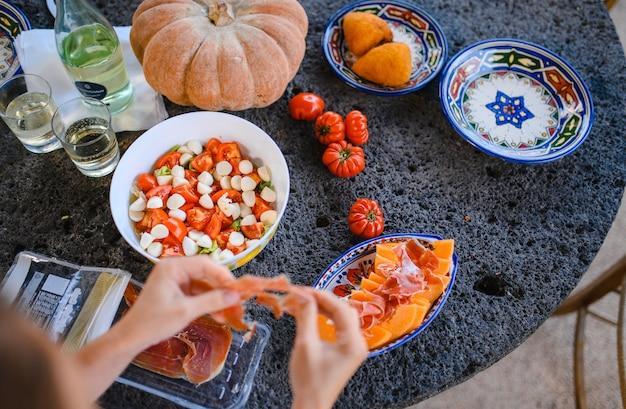 La ragazza sta preparando antipasto prosciutto e melone Foto Premium