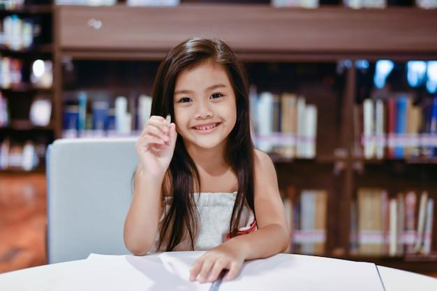 La ragazza sta studiando in biblioteca Foto Premium