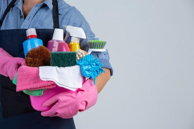 La ragazza sta tenendo il prodotto, i guanti e gli stracci di pulizia nel bacino sulla parete bianca Foto Gratuite
