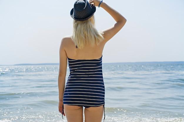 La ragazza sulla spiaggia in costume da bagno e cappello guarda il mare, il concetto di tempo libero. mare, spiaggia, estate. il tempo si rilassa. Foto Premium