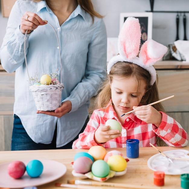 La ragazza sveglia che dipinge le uova per pasqua vicino alla madre con il piccolo canestro Foto Gratuite