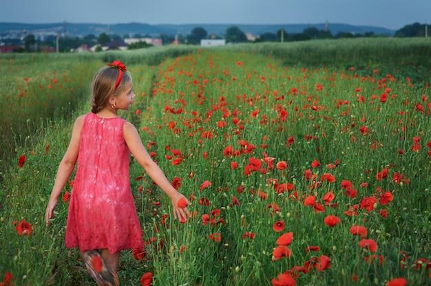 La ragazza sveglia in vestito rosso cammina al campo del papavero Foto Premium