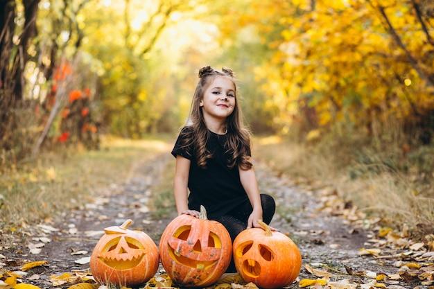 La ragazza sveglia si è vestita in costume di halloween all'aperto con le zucche Foto Gratuite