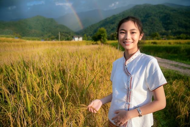 La ragazza tailandese cammina sull'azienda agricola del riso e della risaia nella caffetteria lamduan del panno tessuto Foto Premium