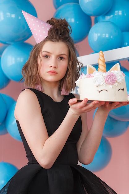 La ragazza teenager felice che tiene l'unicorno ha messo a strati il dolce decorato con il primo piano delle meringhe. Foto Gratuite