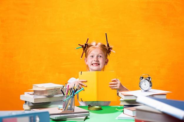 La ragazza teenager rossa con molti libri a casa. Foto Gratuite