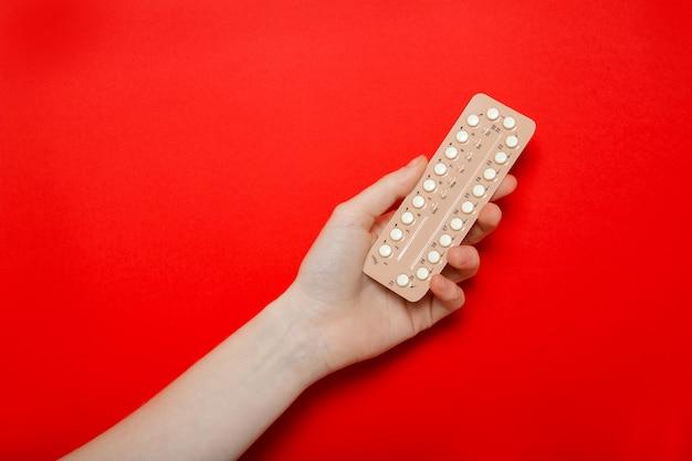 La ragazza tiene in mano le pillole anticoncezionali. contraccezione. muro rosso, posto per il testo. Foto Premium