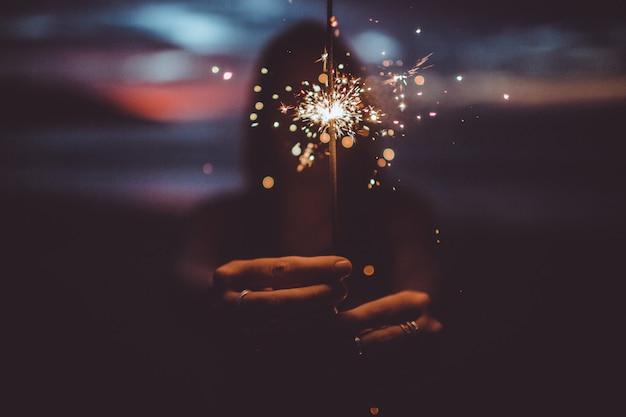 La ragazza tiene in mano un fuoco di bengala Foto Gratuite