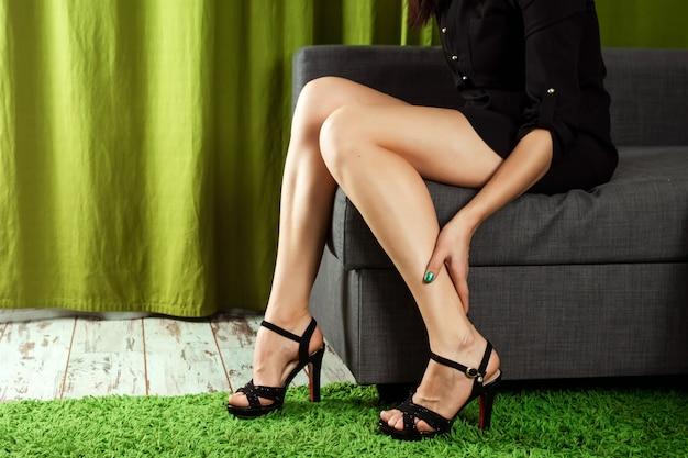 La ragazza tiene le gambe, il dolore alle gambe dai talloni Foto Premium