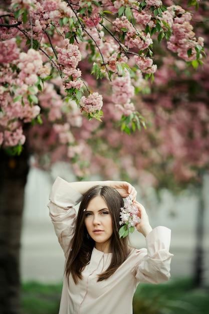 La ragazza tiene le mani dietro la testa con il ramo di sakura Foto Gratuite