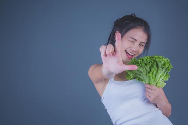 La ragazza tiene le verdure su uno sfondo grigio. Foto Gratuite