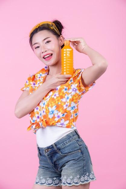 La ragazza tiene una bottiglia di succo d'arancia su uno sfondo rosa. Foto Gratuite