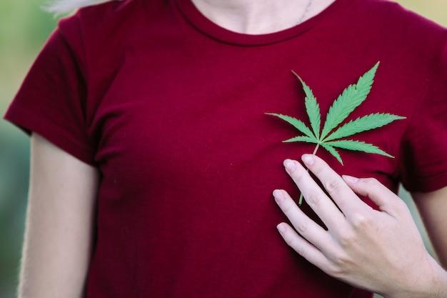 La ragazza tiene una foglia di marijuana sul petto. Foto Premium