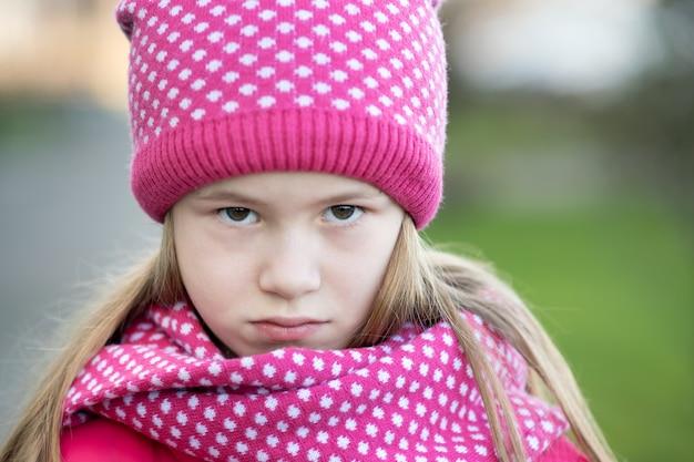 La ragazza triste del bambino nell'inverno tricottato caldo copre all'aperto. Foto Premium