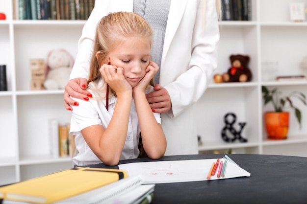 La ragazza triste si siede al tavolo, disegna, sua madre abbraccia le sue spalle e conforta Foto Premium