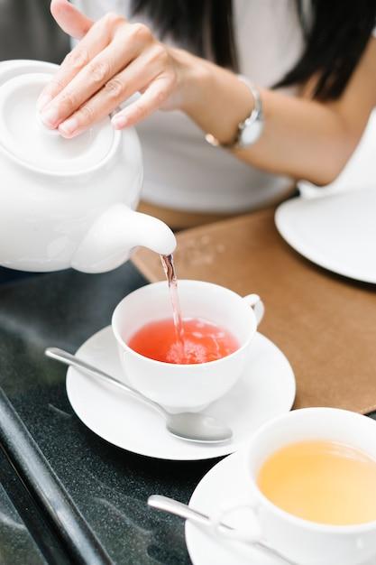 La ragazza versa il tè lentamente Foto Gratuite